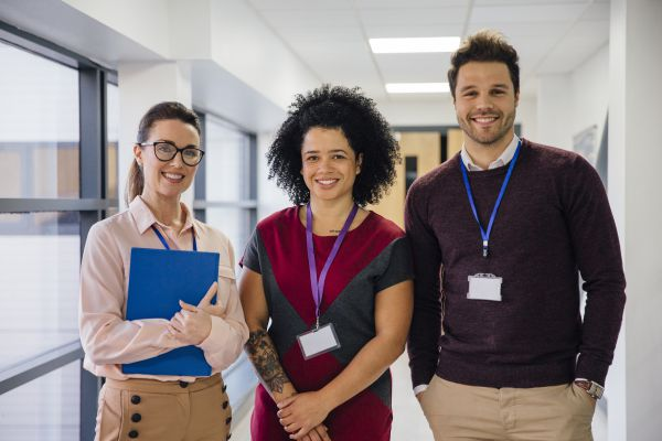 Three teachers in a school hallway