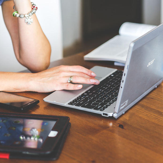 A woman's hand on the keyboard of a laptop