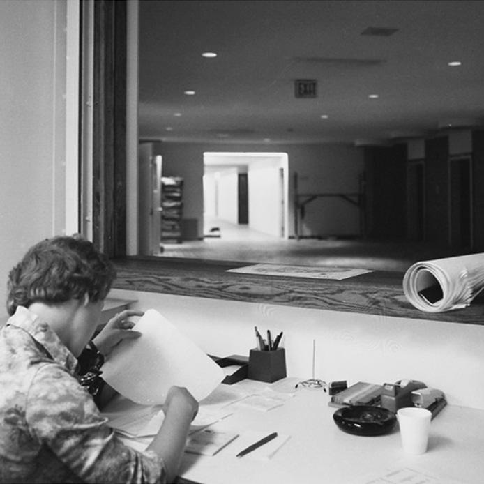 Une femme lit des papiers à son bureau