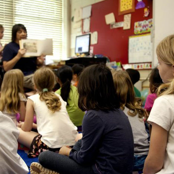A teacher reads aloud to a group of young students