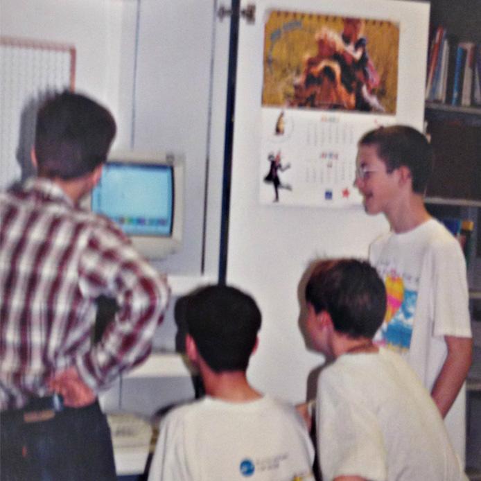 Deux enfants regardent un adulte avec son ordinateur