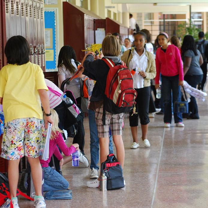 Des étudiants d'une école primaire jouent et parlent dans un corridor