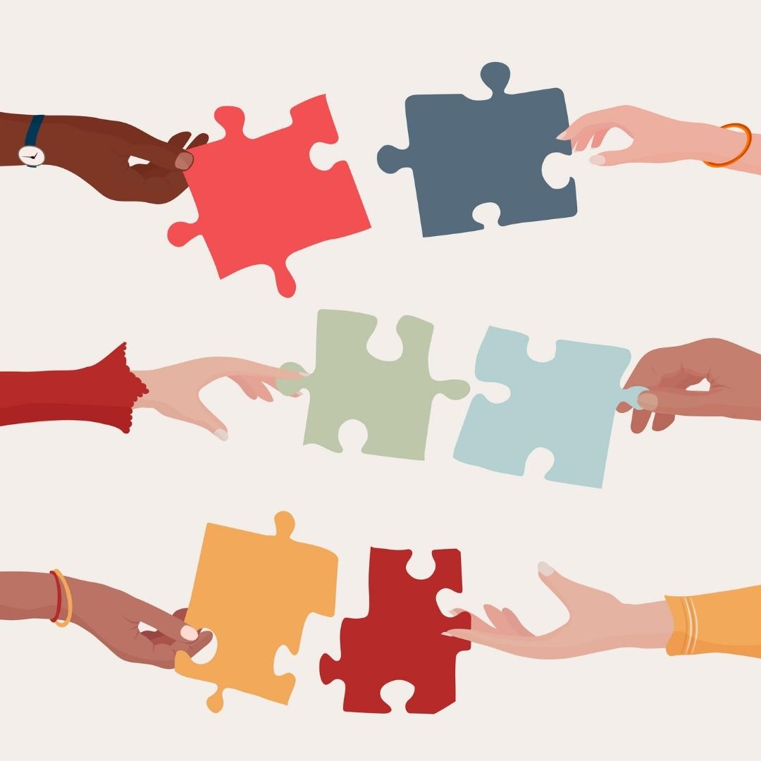 Mains de différentes couleurs tenant des pièces de puzzle