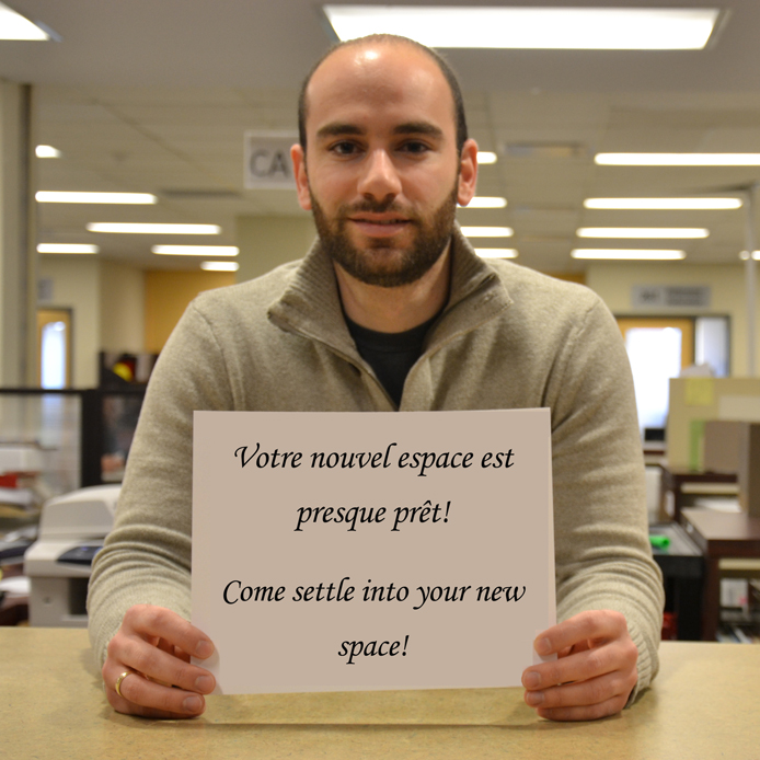 "Here we see a member of the Resource Centre holding a sign that says ""Come settle into your new space"""