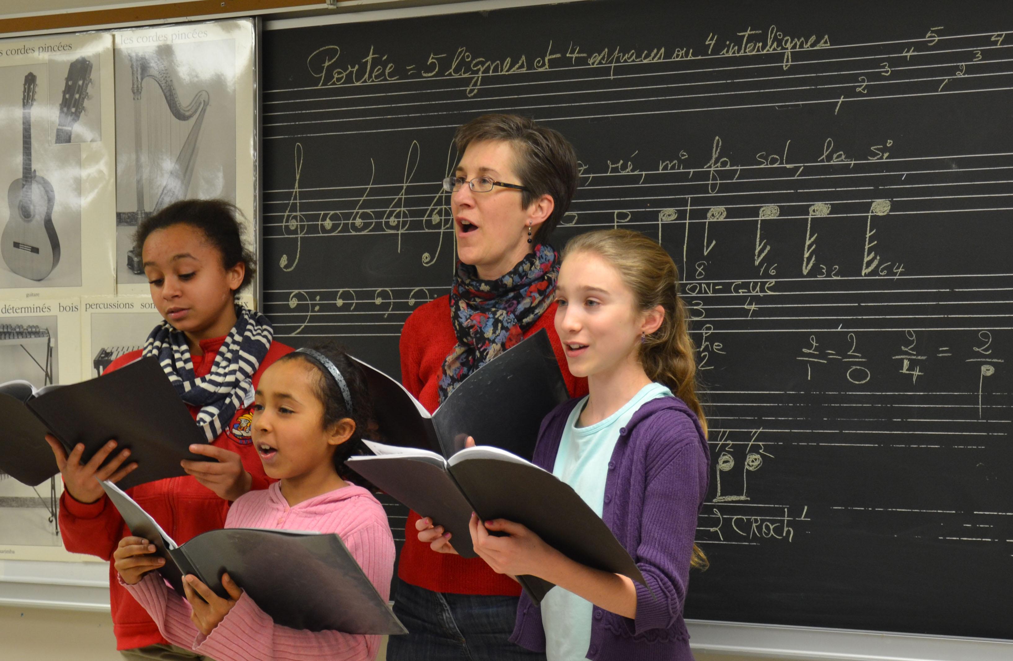 Quatre membres femelles de la chorale chantent devant une salle de classe
