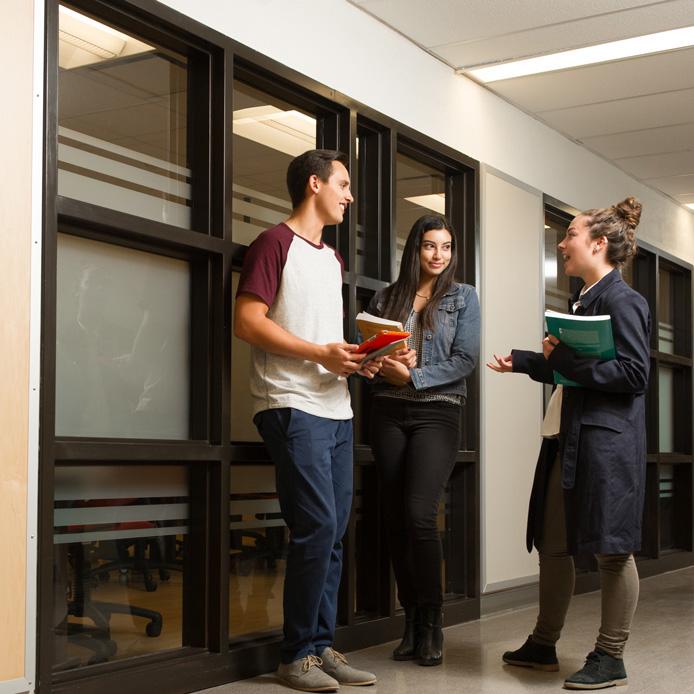Un jeune homme et deux jeunes femmes tenant des cahiers scolaires discutent dans un couloir devant de grandes vitres.