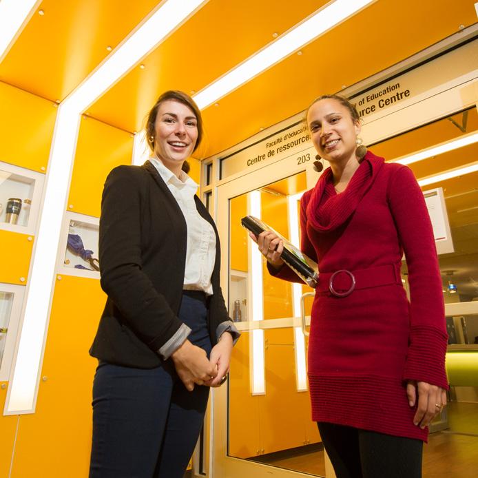 Deux jeunes femmes habillées professionnellement se tiennent devant la porte d'entrée du Centre de ressources de la Faculté d'éducation.