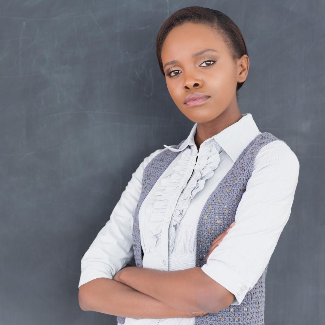 Female Teacher standing in front of a chalkboard
