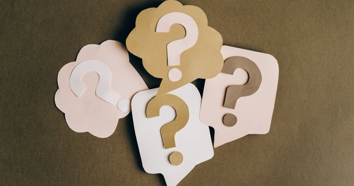 Question marks on brown paper background