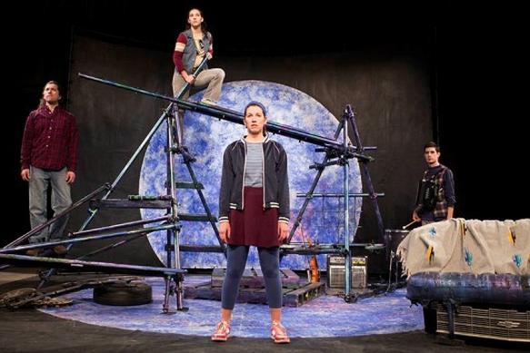 une actrice se tient debout sur une étage avec trois acteurs derrière elle regardant vers la distance