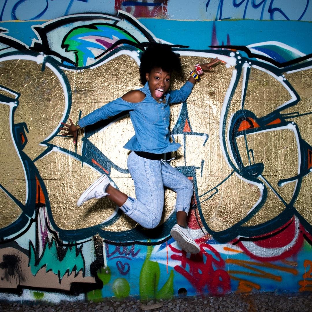 Pearline Barrett-Fraser danse devant un mur coloré