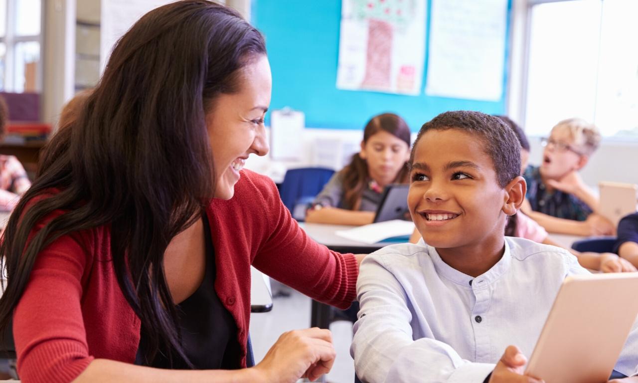 Une enseignante sourit à un jeune étudiant en classe