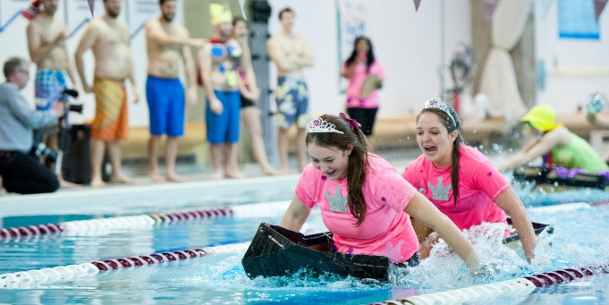 Students in a cardboard boat in a pool